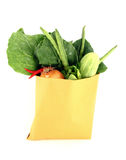 Assorted vegetables in brown bag. Isolated over white background Royalty Free Stock Photography