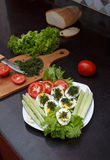 Assorted vegetables and eggs with a chopping board and a knife Royalty Free Stock Images