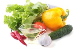 Assorted vegetables, fresh bell pepper, tomato, chilli pepper, cucumber, olive oil, garlic and lettuce  on white Stock Photography