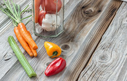 Assorted vegetables lying on old wood background. Horizontal image of assorted vegetables in a clear glass jar with carrots and celery and peppers lying on one Stock Photo