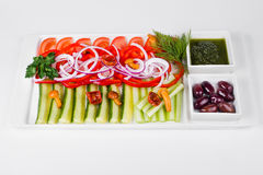 Assorted vegetables with sliced cucumber, tomatoes, chili, onion. Olive and mushroom on white background deliciously Stock Image