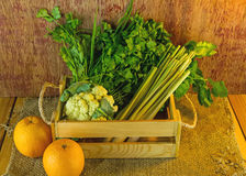 Assorted vegetables in wood box on dark rustic wooden and sack s. Isal background in dark tone Royalty Free Stock Photo