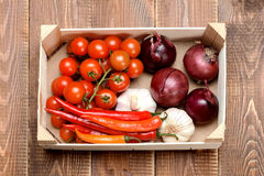 Assorted vegetables in a wooden crate on a wooden background. Stock Image