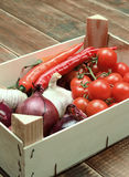 Assorted vegetables in a wooden crate on a wooden background. Royalty Free Stock Image