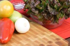 Assorted veggies on fine wood cuttingboard Royalty Free Stock Photos