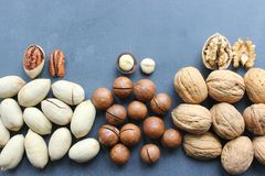 Assorted Walnuts, macadamia nuts and pecans close-up on wooden table. Assorted Walnuts, macadamia nuts and pecans close up on wooden table. Healthy food, cafe royalty free stock images