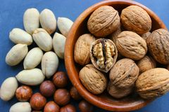 Assorted Walnuts, macadamia nuts and pecans close-up on wooden table. Assorted Walnuts, macadamia nuts and pecans close up on wooden table. Healthy food, cafe royalty free stock photos