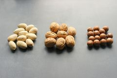 Assorted Walnuts, macadamia nuts and pecans close-up on wooden table. Assorted Walnuts, macadamia nuts and pecans close up on wooden table. Healthy food, cafe stock image