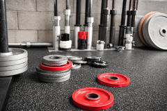 Assorted weights scattered on the floor of a gym. Assorted weights of different sizes for a barbell lying scattered on the floor of a crossfit gym in a health royalty free stock photography
