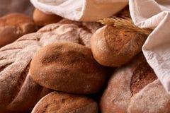 Assortement av nytt bröd med den vita torkduken och öron av vete Royaltyfria Bilder