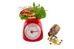 Assorti de fines herbes dans l'échelle rouge de poids et les pilules colorées dans le bl Photographie stock