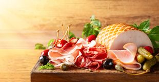 Assorti of sliced jamon, salami, ham with olives ,capers, pickles and stuffed red peppers royalty free stock photography