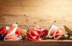 Assorti of sliced jamon, salami, ham with olives ,capers, pickles and stuffed red peppers stock photography