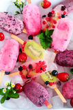 Assortiment de Berry Popsicles avec les feuilles en bon état sur des glaçons Photos stock