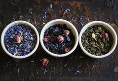 Assortiment de thé sec dans des cuvettes blanches Photo stock