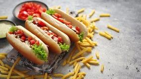 Assortiment de trois hot-dogs tasety, placé sur la planche à découper en bois banque de vidéos