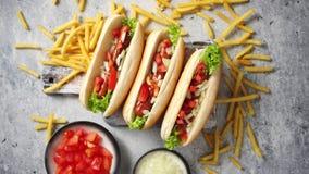 Assortiment de trois hot-dogs tasety, placé sur la planche à découper en bois clips vidéos
