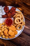 Assortiment des anneaux d'oignon frits de casse-croûte, ailes de poulet avec de la sauce images libres de droits