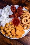 Assortiment des anneaux d'oignon frits de casse-croûte, ailes de poulet avec de la sauce photos stock