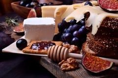 Assortiment des apéritifs : différentes sortes de fromage, de biscuits, de raisins, d'écrous, de confiture d'oranges olive, de fi image stock