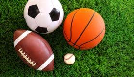 Assortiment des billes de sport sur l'herbe Photographie stock