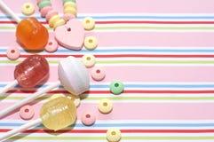 Assortiment des bonbons sur le fond rayé Image stock