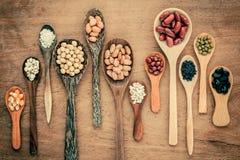 Assortiment des haricots et des lentilles dans la cuillère en bois sur le CCB en bois de teck Photos stock
