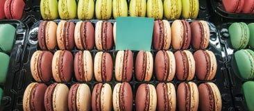Assortiment des macarons dans un récipient en plastique en vente dans une pâtisserie image stock
