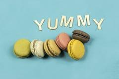 Assortiment des macarons multicolores sur un fond bleu avec le mot délicieux Image libre de droits