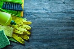 Assortiment des objets de nettoyage de ménage sur le panneau en bois de cru images libres de droits
