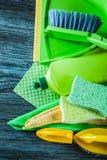 Assortiment des outils de nettoyage de ménage sur le conseil en bois image stock