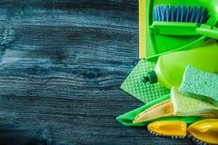 Assortiment des outils de nettoyage de ménage sur le panneau en bois de cru images stock