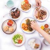 Assortiment des plats : satay avec de la sauce à beurre d'arachide, le wonton frit, le poulet grillé et le canard, légumes faits  Image stock
