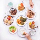 Assortiment des plats : satay avec de la sauce à beurre d'arachide, le wonton frit, le poulet grillé et le canard, légumes faits  Images libres de droits