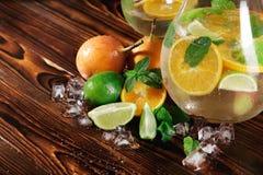 Assortiment en gros plan des agrumes Menthe, glace et fruits sur un fond brun Ingrédients exotiques pour des gourmets et des vega photographie stock