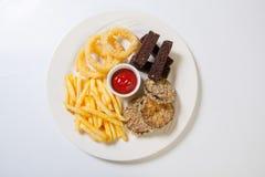 Assortiment frais de casse-croûte de bière d'un plat blanc Pommes frites, croûtons et courgette Photo libre de droits
