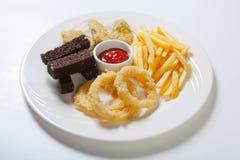 Assortiment frais de casse-croûte de bière d'un plat blanc Pommes frites, croûtons et courgette et anneaux d'oignon Images stock