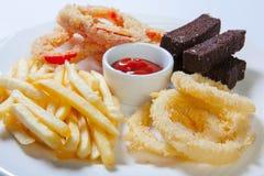 Assortiment frais de casse-croûte de bière d'un plat blanc Pommes frites, croûtons et courgette et poivron doux Photographie stock