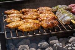 Assortiment mélangé de viande, de poulet, et de crevettes roses marinés grillant sur les charbons chauds sur un BBQ image libre de droits