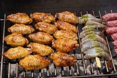 Assortiment mélangé de viande, de poulet, et de crevettes roses marinés grillant sur les charbons chauds sur un BBQ images libres de droits