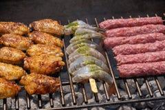 Assortiment mélangé de viande, de poulet, et de crevettes roses marinés grillant sur les charbons chauds sur un BBQ images stock