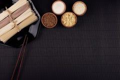 Assortiment van bundels ruwe noedels met ingrediënt in houten kommen op zwarte gestreepte matachtergrond met exemplaar ruimte, ho Royalty-vrije Stock Fotografie