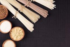 Assortiment van bundels ruwe noedels met ingrediënt in houten kommen op zwarte gestreepte matachtergrond met exemplaar ruimte, ho Royalty-vrije Stock Afbeelding