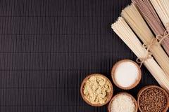 Assortiment van bundels ruwe noedels met ingrediënt in houten kommen op zwarte gestreepte matachtergrond met exemplaar ruimte, ho Stock Foto's