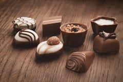 Assortiment van chocolade op houten achtergrond stock afbeeldingen