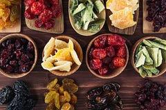 Assortiment van droge vruchten in lepels, kommen op bruine houten achtergrond Royalty-vrije Stock Foto's