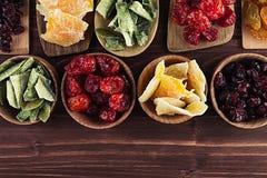 Assortiment van droge vruchten in lepels, kommen op bruine houten achtergrond Stock Foto's