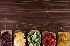 Assortiment van droge vruchten in lepels op bruine houten achtergrond Stock Fotografie