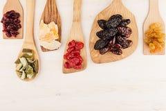 Assortiment van droge vruchten op houten lepels op witte achtergrond Stock Foto
