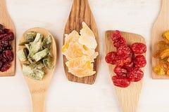 Assortiment van droge vruchten op houten lepels op witte achtergrond Royalty-vrije Stock Afbeeldingen